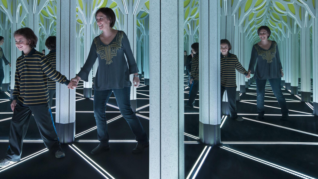 Guests walking through the mirror maze in the Numbers in Nature exhibit