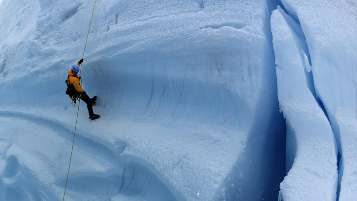 Photo of a man climbing a glacier from the Extreme Ice exhibit