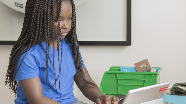 Young girl works on a laptop